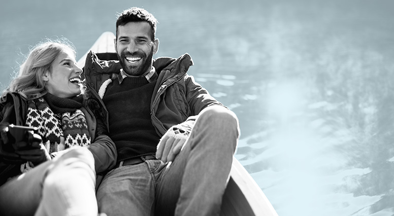 Young couple next to each other at the back of a canoe