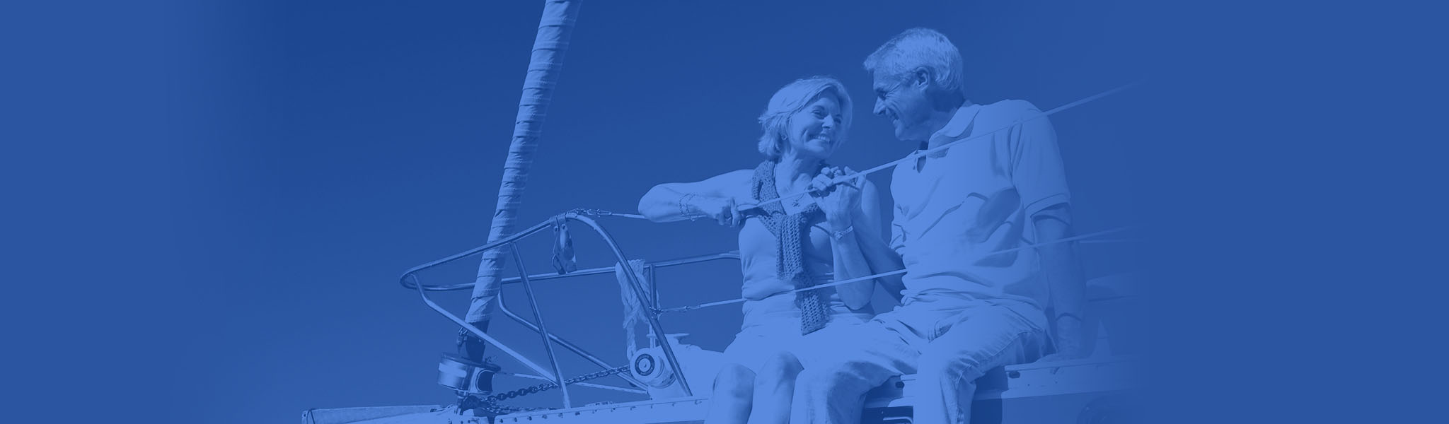 A retired couple on their sailboat smile at each other