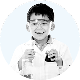 A kid dressed as a lab scientist  is smiling while holding an erlenmeyer flask and a test tube