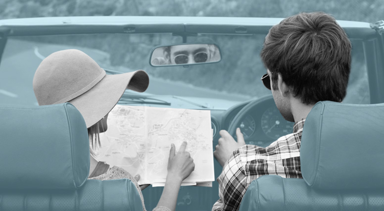 In a convertible, a couple consults a road map