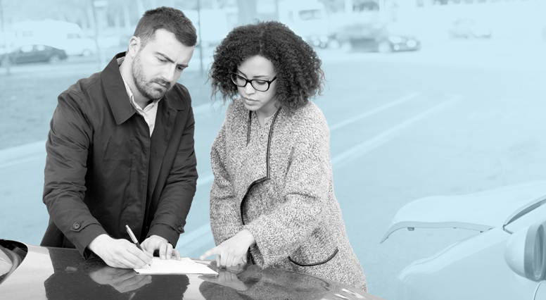 A driver writes an accident report with a female driver