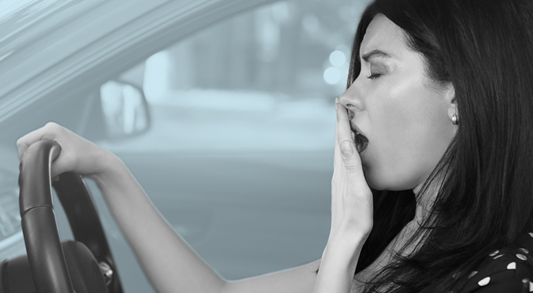 Woman yawns behind the wheel of her car