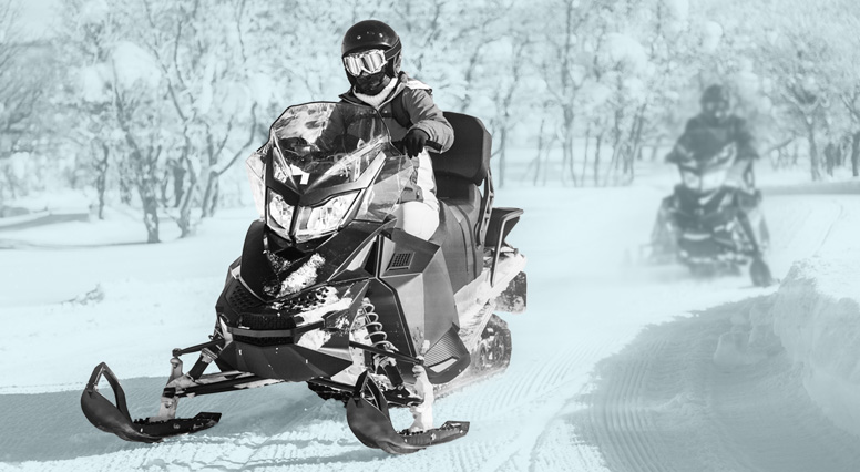 Two snowmobilers follow each other on a trail