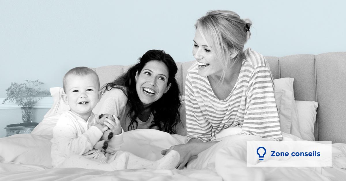 deux femmes souriantes et un bébé sur un lit