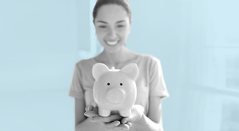 Woman looks at her piggy bank smiling