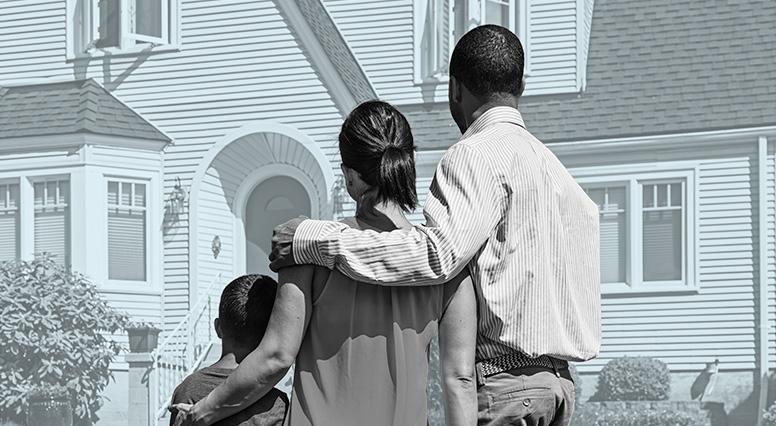 Un couple et leur enfant regardent une maison