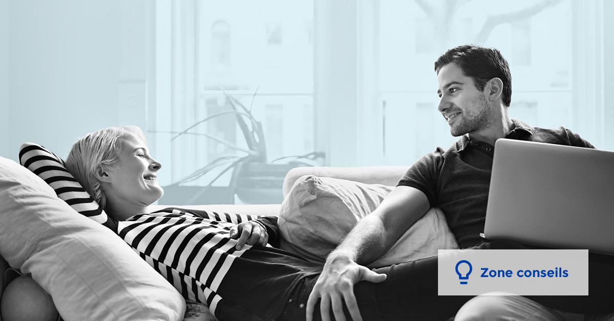 Une femme et un hommes sont confortablement assis sur un canapé et ils se sourient l'un l'autre