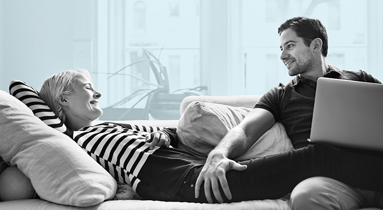 A woman and a man are comfortably seated on a couch and they smile at each other