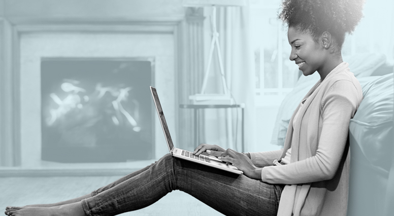 Une jeune femme est assise avec un ordinateur portatif sur ses genoux