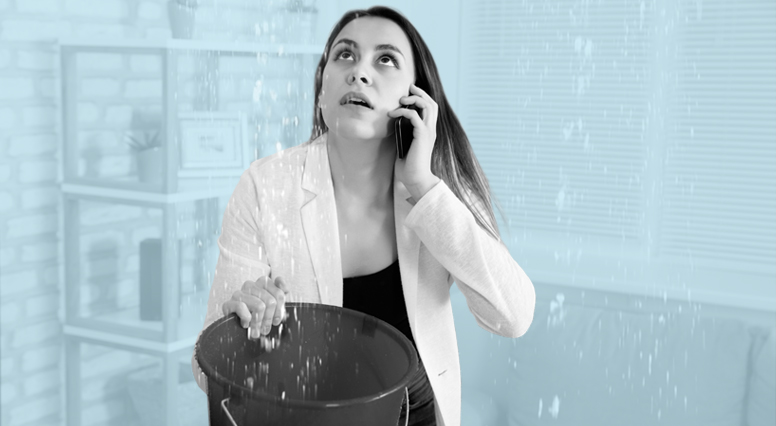 Une femme place un seau sous une fuite d'eau