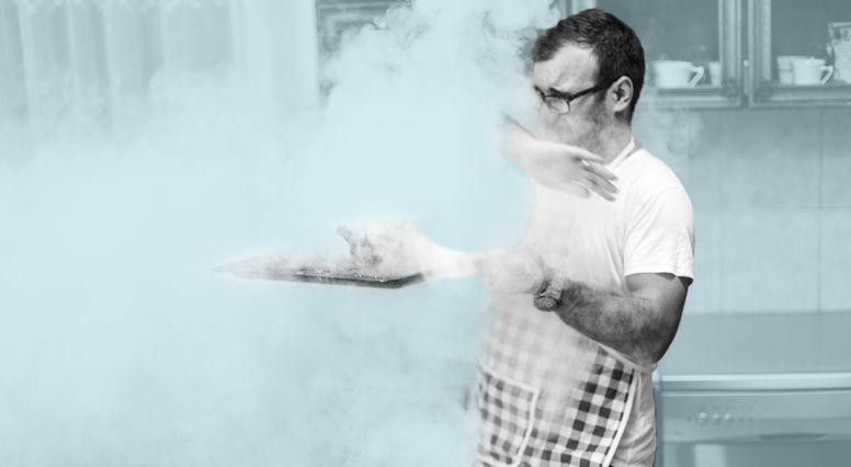 Un homme sort du four de la nourriture en train de brûler
