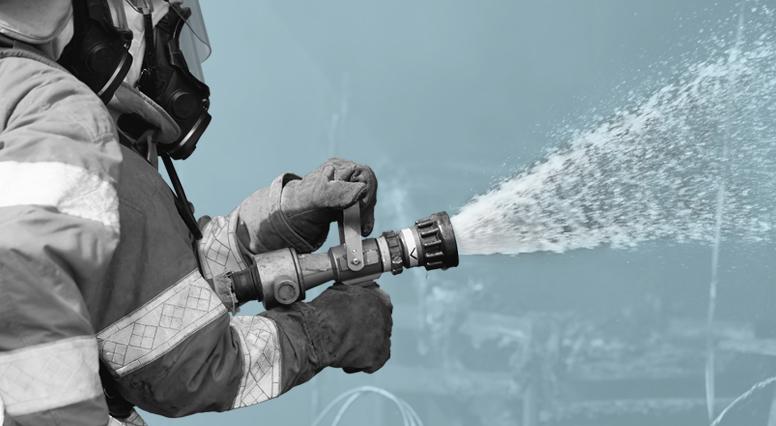 Gros plan d'un pompier maniant le boyau