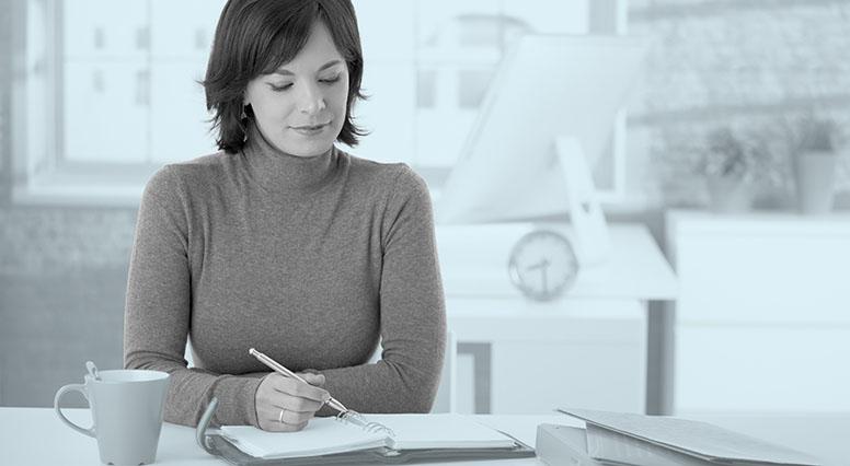 Une femme écrit en prenant un café