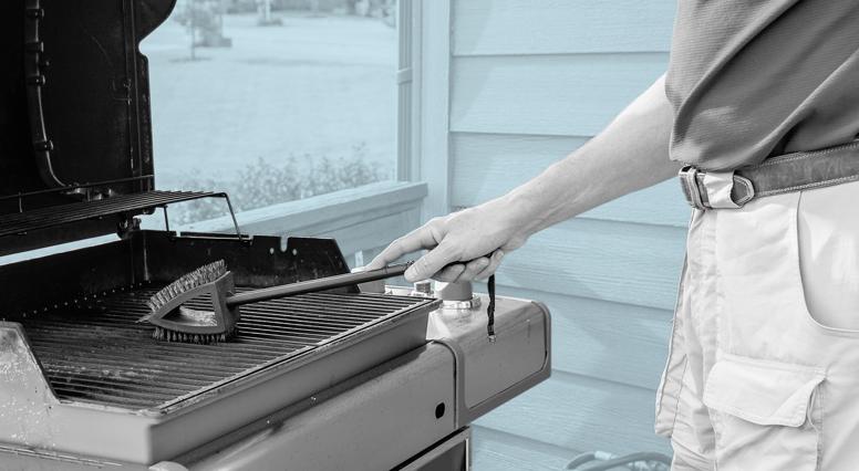 Un homme nettoie les grilles de son barbecue