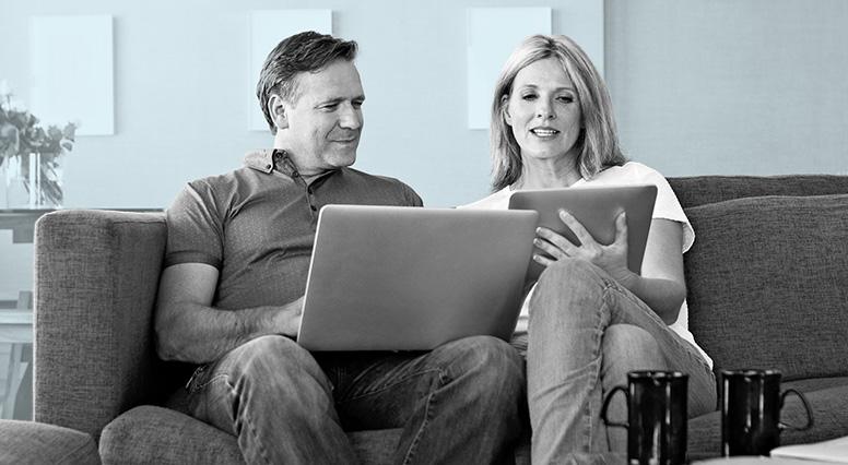 Un couple assit sur un canapé discute en regardant leurs ordinateurs portatifs