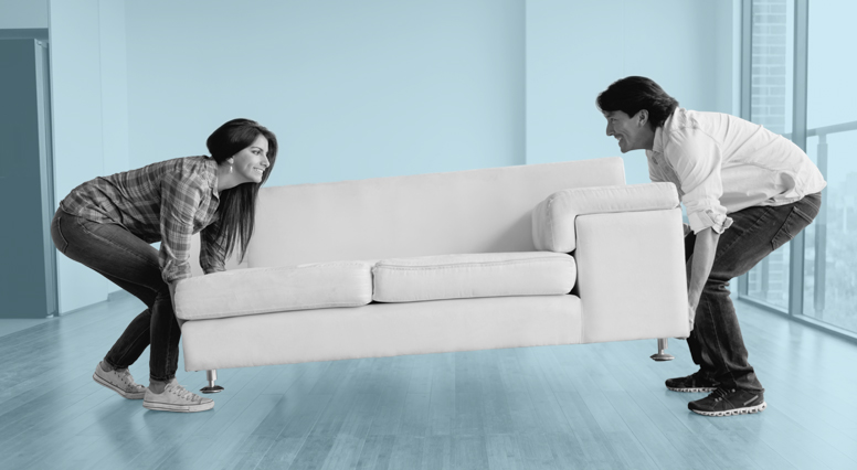 A woman and a man install their couch in their living room