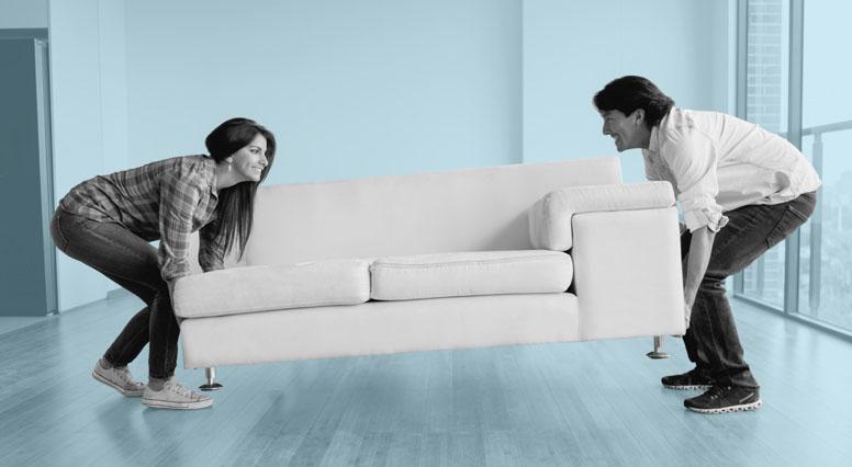 Une femme et un homme installent leur divan dans leur salon