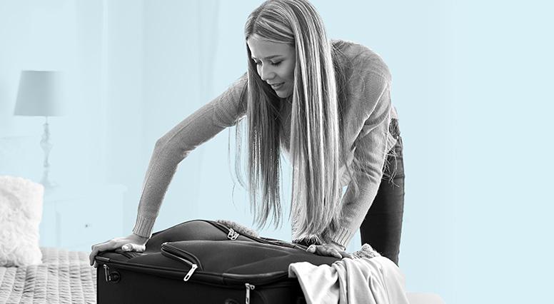 Jeune femme qui fait ses bagages