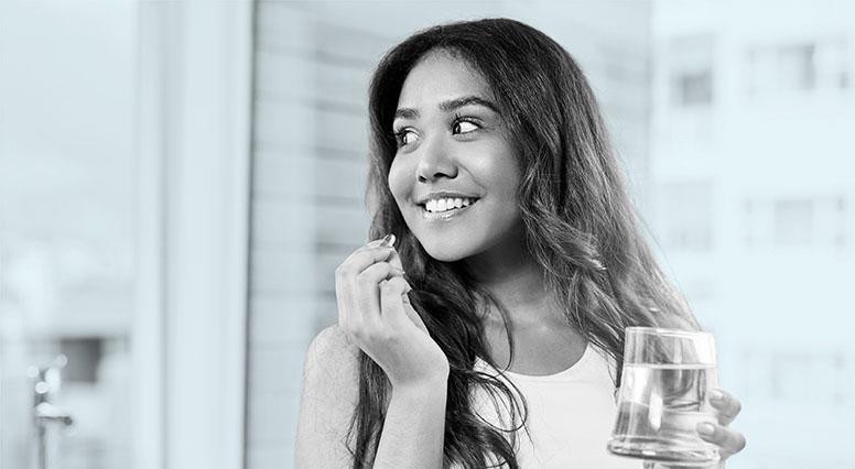 Jeune femme qui prend un médicament avec un verre d'eau