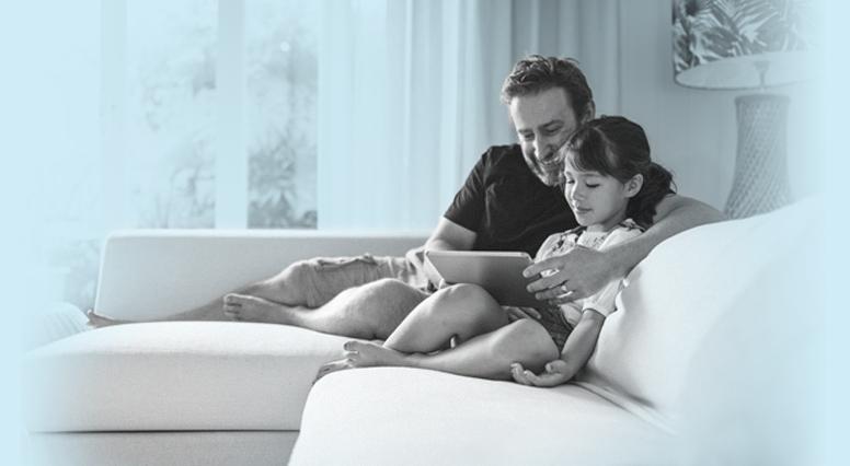 Une père et sa fille sur le divan consulte une tablette électronique